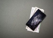 Defekter Handy mit Geld auf Grün stockbilder