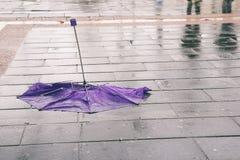 Defekter Regenschirm auf nassem Bürgersteig Stockbild