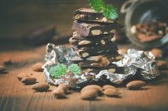 Defekter Schokoriegel, tadellose Blätter und Mandeln Stockfotos