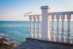 Defekter weißer Balkon auf Terrasse nahe Meer und blauem Himmel Lizenzfreies Stockfoto