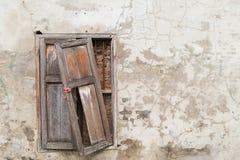 Defektes altes Fenster auf alter gebrochener Wand Stockfotografie