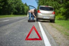 Defektes Auto, Rettungszeichen und Mann mit Ersatzrad lizenzfreie stockfotos