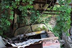 Defektes Boot in den grünen Blättern lizenzfreie stockbilder