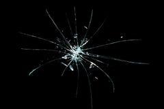 Defektes gebrochenes Glas mit Loch über schwarzem Hintergrund Lizenzfreie Stockfotos
