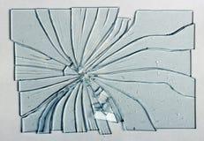Defektes Glas auf einem grauen Hintergrund Stockfotografie