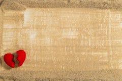 Defektes Herz auf dem Sand, der gefegt wird Stockbild