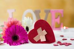 Defektes Herz mit Liebe und Blumen Stockfotografie