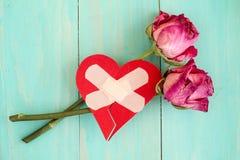 Defektes Herz und alte Rosen Stockbild