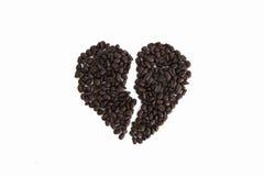 Defektes Herz von den Kaffeebohnen lokalisiert auf einem weißen Hintergrund Lizenzfreies Stockfoto