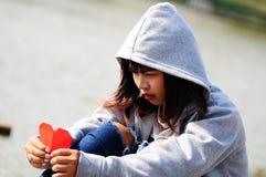 Defektes herziges Mädchen, das rotes Papierherz sieht lizenzfreies stockfoto