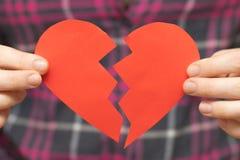 Defektes herziges Roter heart-shaped Schmucksachegeschenkkasten und eine rote Spule auf einem Zeichen Frau, die gebrochenes hea h Lizenzfreies Stockfoto