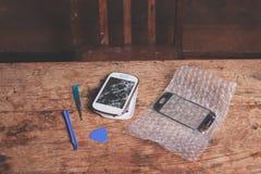 Defektes intelligentes Telefon und Werkzeuge Stockfoto