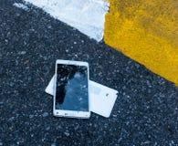 Defektes neues Smartphone auf Asphaltstraße Jemand ließ Gerät fallen Sprünge auf einer großen Anzeige Lizenzfreie Stockfotografie