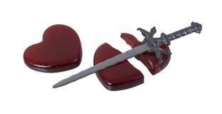 Defektes rotes Glasherz mit einer Klinge Stockfoto