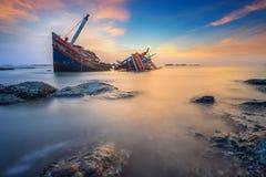 Defektes Schiff über dem Meer mit dem Sonnenunterganghimmel Lizenzfreies Stockfoto