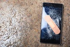 Defektes Telefon mit dem gebrochenen Schirm geregelt mit haftendem Gips Co Stockfotografie