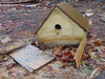 Defektes Vogelhaus gegen die toten Blätter lizenzfreie stockfotos