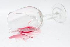 Defektes Weinglas mit verschüttetem Spritzen des Rotweins stockfotos