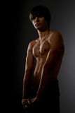 Defender of the Faith. Topless strong young man with cross on a chain shot in studio in low-key lightning stock images
