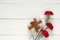 Defender of the Fatherland Day. Red carnations and gift box with. St george ribbons on the white background. Space for text stock images