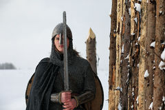 Defender the young warrior in mail armor armed with a sword Stock Photos