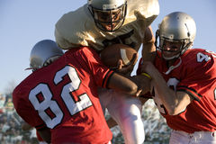 Defenders tackling running back carrying football Royalty Free Stock Photography