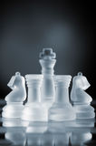 Defending the queen. Glass chess pieces are defending the queen on board in dark royalty free stock images