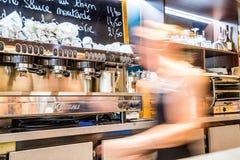 Defensa del La, Francia - 17 de julio de 2016: camarera borrosa en restaurante francés tradicional grande en la ciudad de la defe Fotografía de archivo