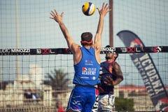Defensa del voleibol de playa del hombre del atleta Pared en la red Brazos para arriba Foto de archivo libre de regalías