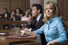 Defense Lawyer With Client In Court. Portrait of a female defense lawyer sitting with client in court room stock photo