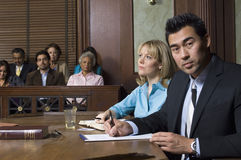 Defense Lawyer With Client In Court. Portrait of a male defense lawyer sitting with client in courtroom Stock Image