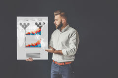 Defense of the thesis. Young bearded businessman, dressed in a white shirt, standing and holding poster with graphs Stock Photography