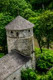 Defense tower in woods. Defense tower and walls of medieval Kamianets-Podilskyi Castle on the Smotrych River bank. A riot of green in May stock photo