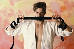 Defensie en taekwondosportenconcept Mens met verborgen gezicht en varkenshaar op kleurrijke achtergrond stock afbeeldingen