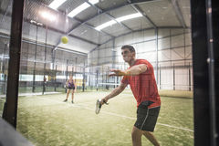 Defensive action in paddle tennis bouncing ball against glass. M Stock Image