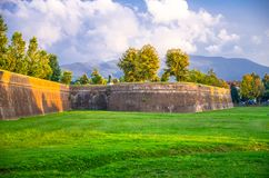 Defensive brick city wall, grass green lawn, trees and Tuscany hills and mountains with beautiful cloudy evening sky background, L. Ucca, Italy stock photos