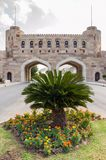 Defensive gates of Old Muscat, Oman. Gates leading into Old Muscat with palm growing in front Royalty Free Stock Image