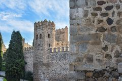 Defensive walls and tower. The defensive stone walls of Toledo, Spain, showing the battlements on top and a guard tower coming into view from behind an even royalty free stock photo