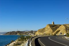 Defensive tower scenery. Road to small spanish village with old defensive tower royalty free stock image
