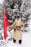 Defensor de Stalingrad en una forma del invierno con una bandera roja Foto de archivo