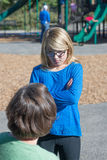 Defiance. A daughter glares at her mother as she lays down the law of proper behavior at a playground Royalty Free Stock Photos