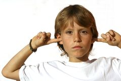 defiant child fingers in ear Stock Photo