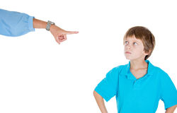 A defiant kid. Closeup portrait of parent pointing at child to go to room for misbehaving while kid is defiant, Isolated on white background Royalty Free Stock Images