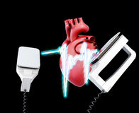 Defibrillator and heart on a black background. Stock Image
