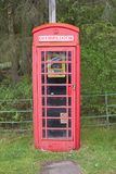 Defibrillator in telephone phone booth box red vintage save life heart attack emergency help in rural countryside Scotland uk royalty free stock photos