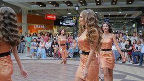 Defile, nice young contestants with long hair in dress and high heels pose on catwalk on beauty contest