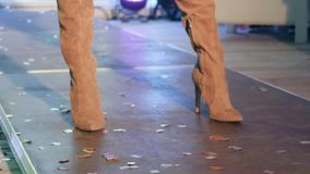 Defile of slender women`s legs in stylish brown boots on podium at fashion show