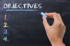 Define business or strategic objectives written by woman on chalkboard. Define business objectives written by woman on chalkboard stock photography