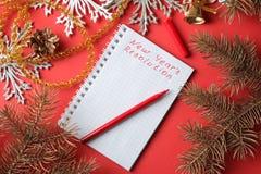 A definição de ano novo das inscrição em um caderno e em umas várias decorações de ano novo em um fundo vermelho Natal do ano nov fotos de stock royalty free