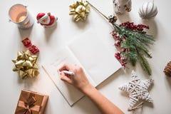 Definições do ano novo escritas com uma mão no caderno com o deco dos anos novos Imagens de Stock Royalty Free
